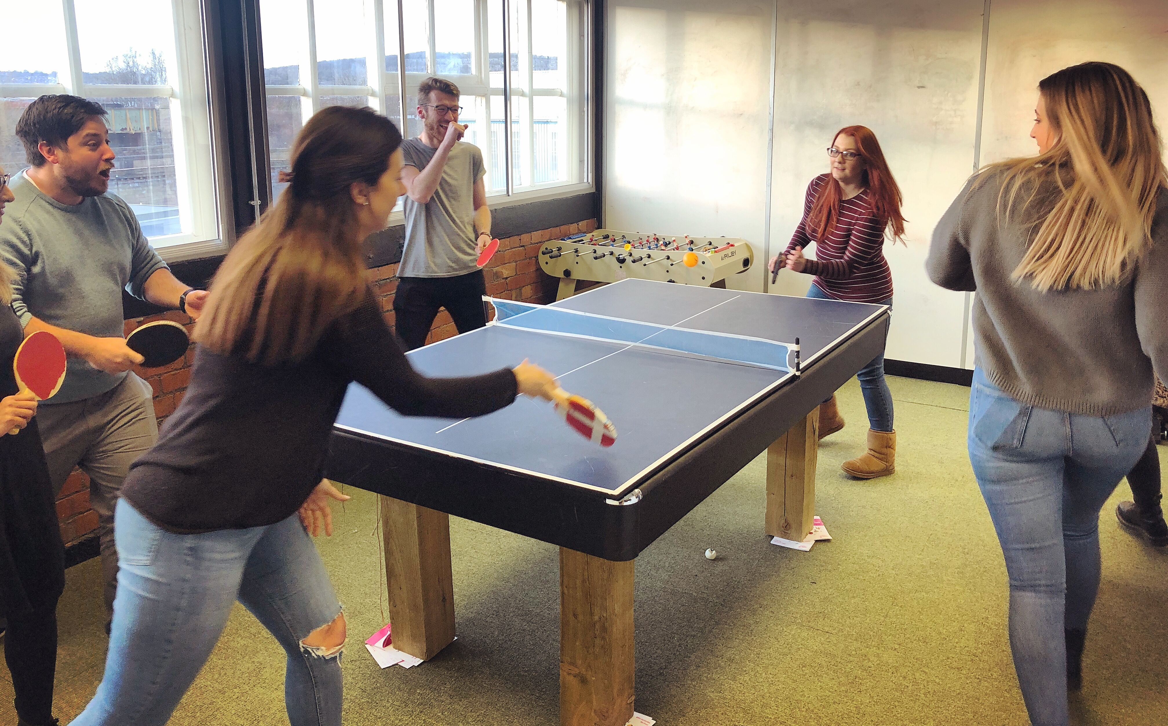 Photo of Split the Bills team playing ping pong