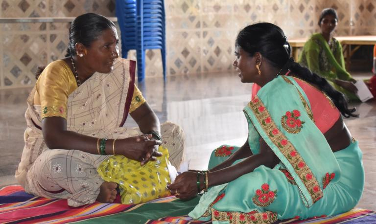 Two women wearing saris sit on the floor in conversation