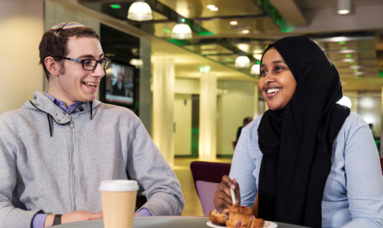 two young people smiling and talking over coffee